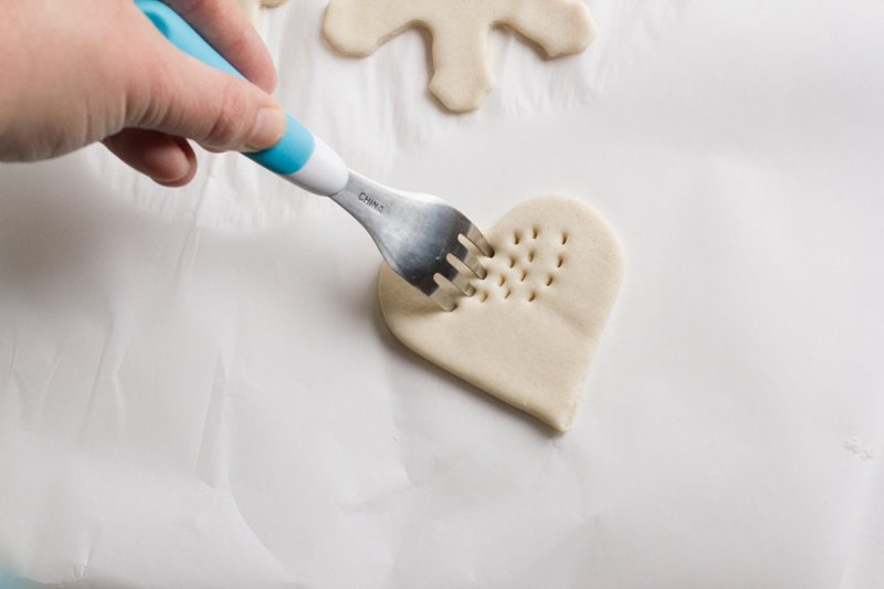 A hand uses a fork to add texture to a heart-shaped salt dough ornament.
