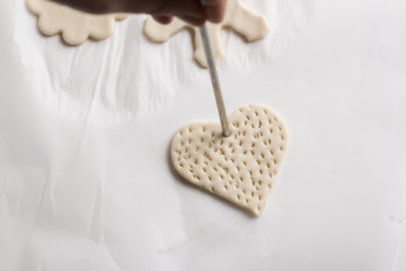A hand uses a straw to poke a hole for a hanging ribbon in a heart-shaped salt dough ornament.