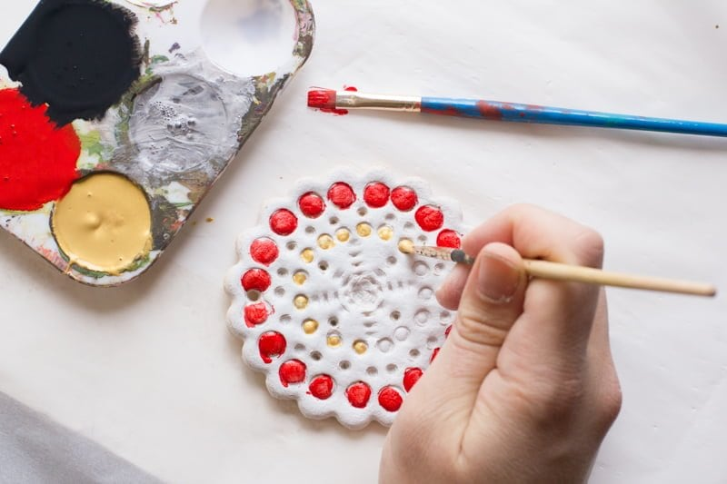 Hand uses a small paintbrush to paint gold details on a salt-dough ornament. A paint palette sits nearby with extra paint brushes.