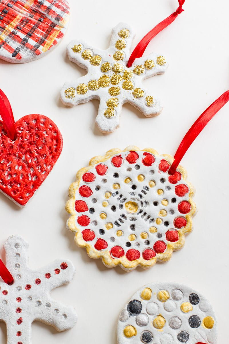 Multiple salt dough ornaments painted in gold, red, and black lie flat on a white background.