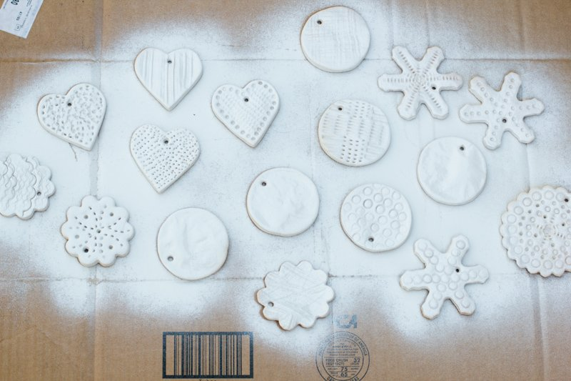 Overhead view of various salt-dough oranment shapes on a piece of cardboard that have been spray painted white.