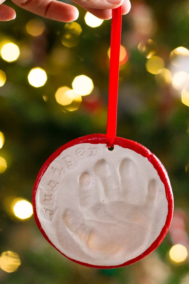 A hand holds a salt dough handprint ornament hanging from a red ribbon. The background is a blurry Christmas tree with lights.