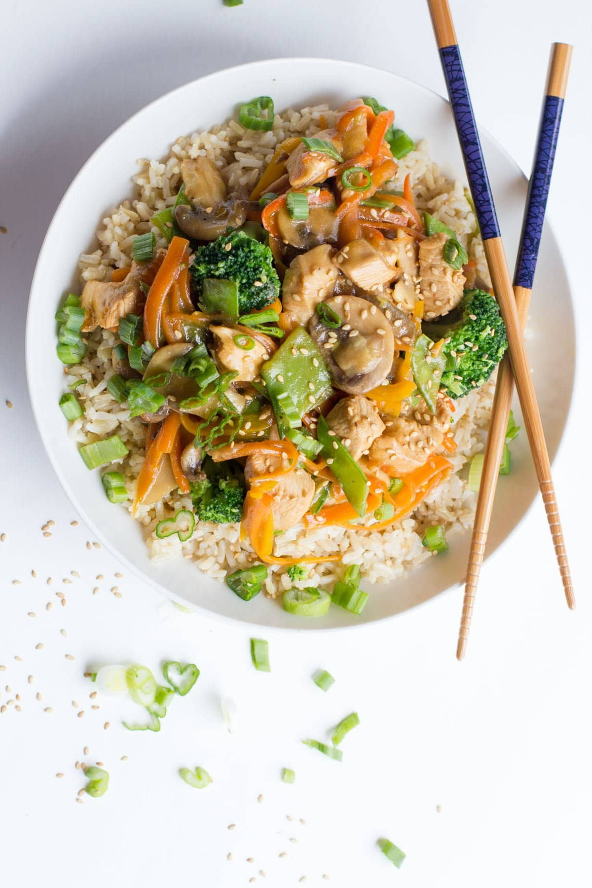 Overhead shot of Healthy Chicken Stir Fry on top of brown rice in a white bowl with crossed chopsticks