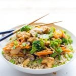 Healthy Chicken Stir Fry on top of brown rice in a white bowl with crossed chopsticks