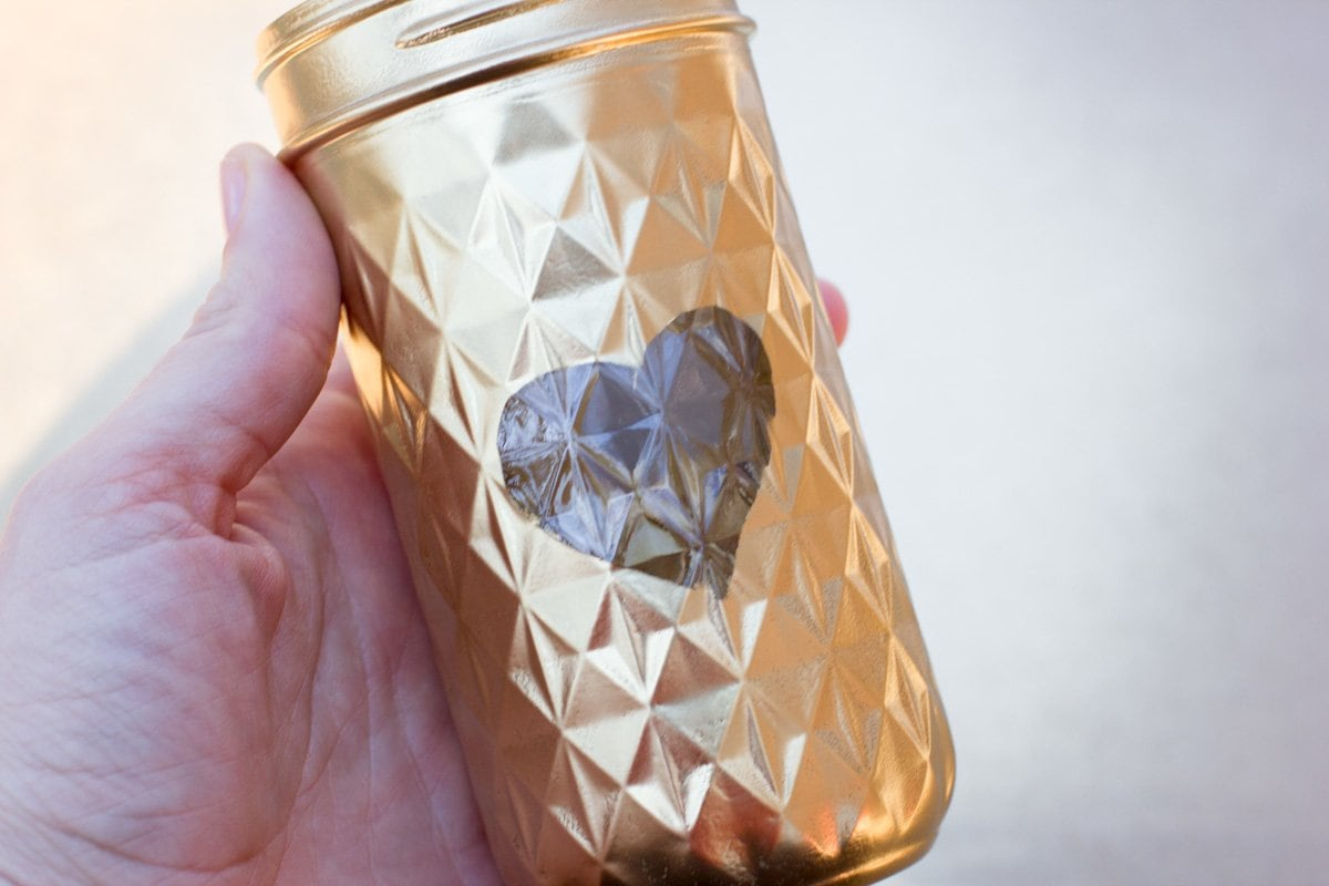 Hand holding a mason jar that has been spray painted gold around a heart shape
