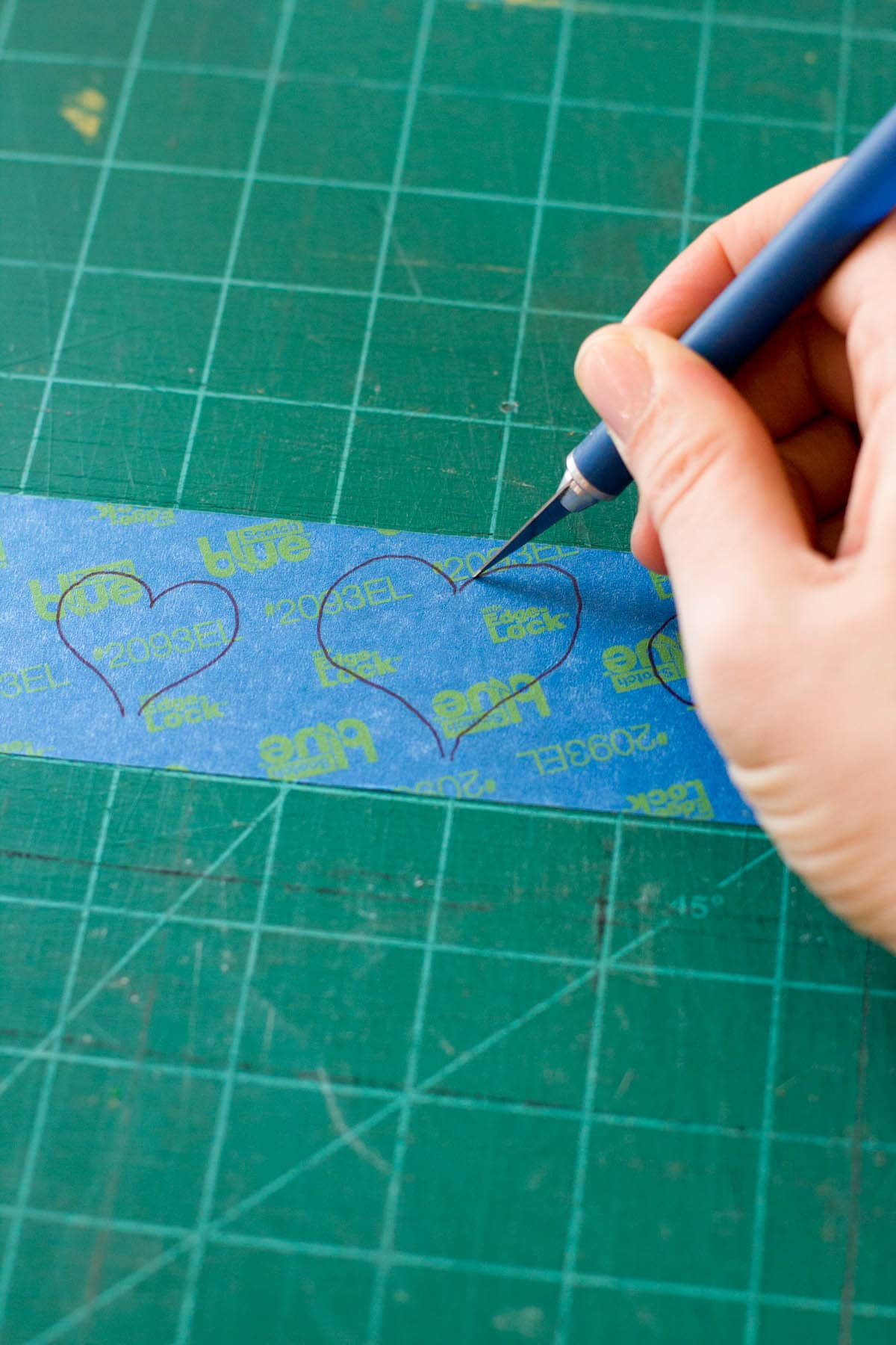 Hand using a craft knife to cut out hearts on a piece of painter's tape