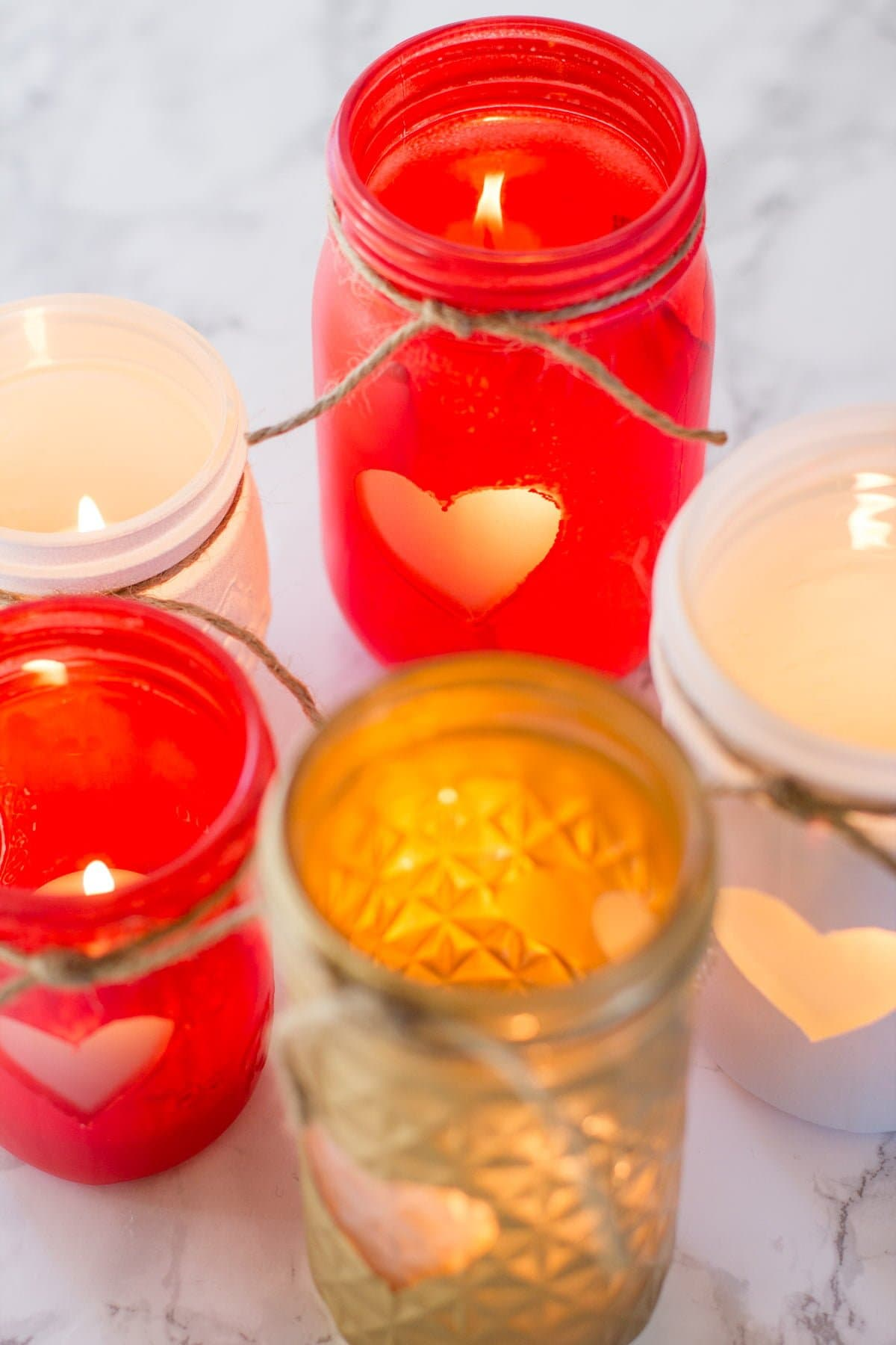 Close-up shot of a cluster of Painted Mason Jar Votive Holders, each with a heart and a piece of twine. The jars are gold, red, and white.