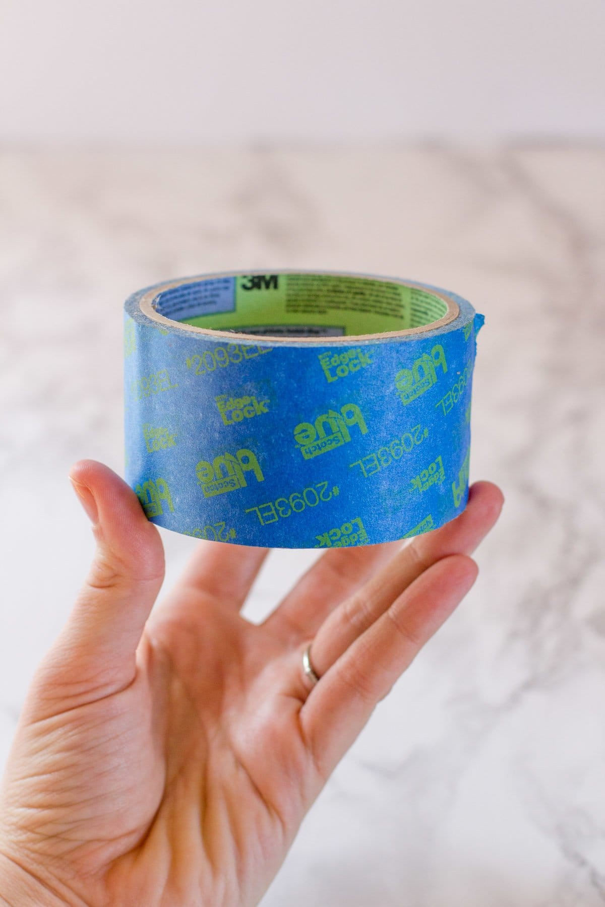 Hand holding up a roll of painter's tape