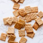 Whole Wheat Parmesan Crackers arranged on a marbled background