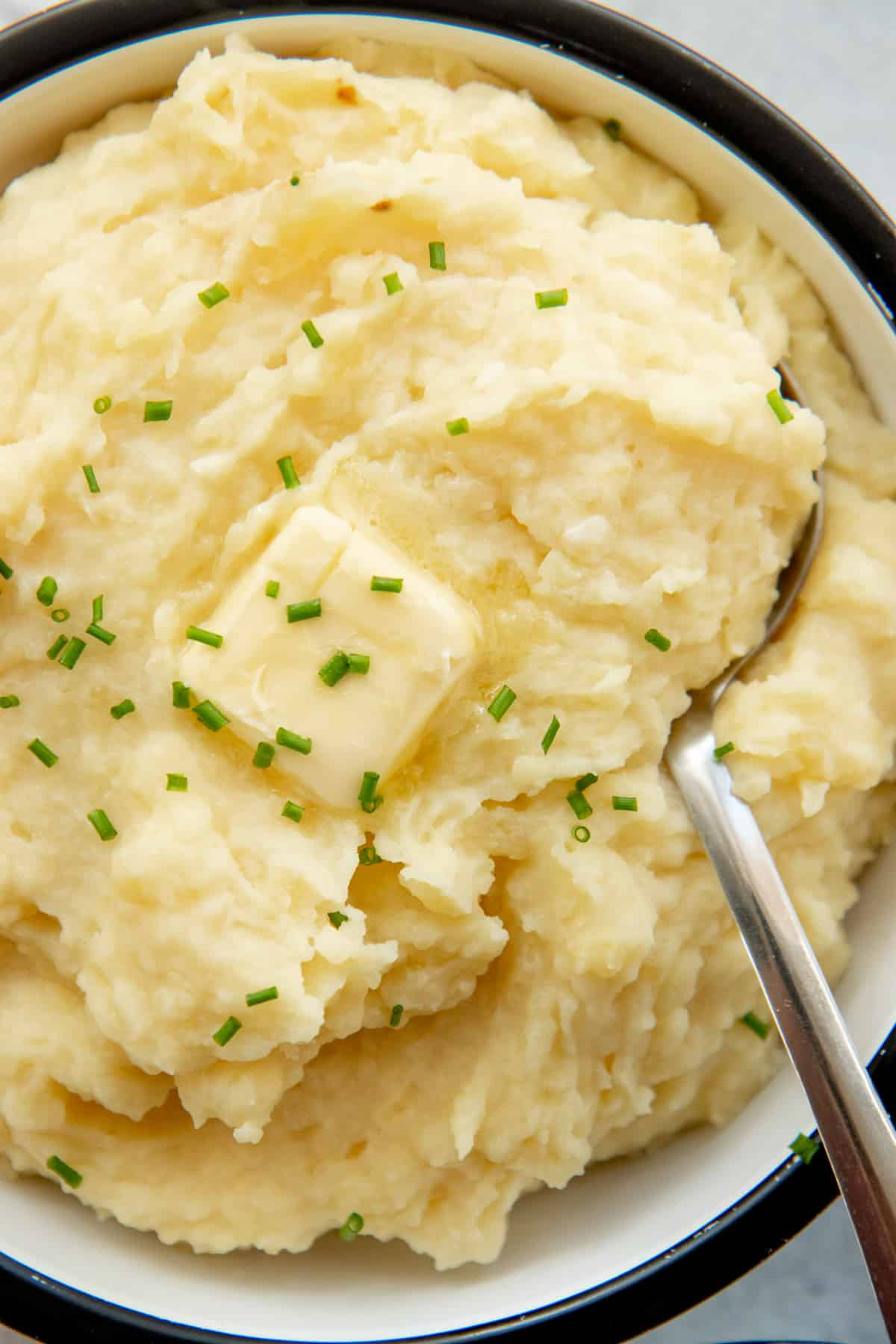 Tight view of creamy mashed potatoes in a bowl with a butter pat melting on top.