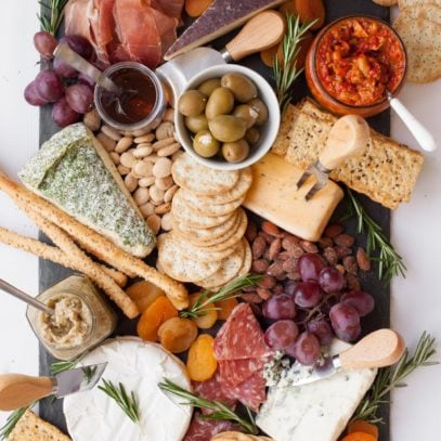 Slate cutting board with 5 wedges of cheese, each with a cheese knife. Various crackers, nuts, dried apricots, olives, condiments, and charcuterie are around the cheese. The board is garnished with fresh rosemary.