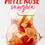 """Glass pitcher filled with sliced fruit and sangria. A text overlay reads """"Autumn Apple Rose Sangria."""""""