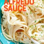 "Noodles with vegan alfredo sauce twirled around a fork. A text overlay reads ""Vegan Alfredo Sauce."""
