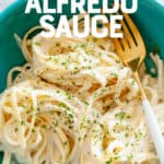 "Turquoise bowl of fettucine noodles in a vegan cashew alfredo sauce. A text overlay reads ""Dairy-Free Alfredo Sauce."""