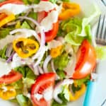 A white bowl is filled with a colorful salad dressed with dairy-free cashew ranch dressing.