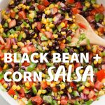 """A white bowl filled with black bean and corn salsa, with a wooden spoon. A text overlay reads """"Black Bean + Corn Salsa."""""""