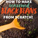 """A pot full of seasoned black beans with a wooden spoon. A text overlay reads """"How to make seasoned black beans from scratch!"""""""