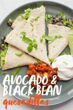 """Quesadilla triangles on a gray plate, with a mound of salsa and a mound of sour cream next to them. A text overlay reads """"Avocado and Black Bean Quesadillas."""""""