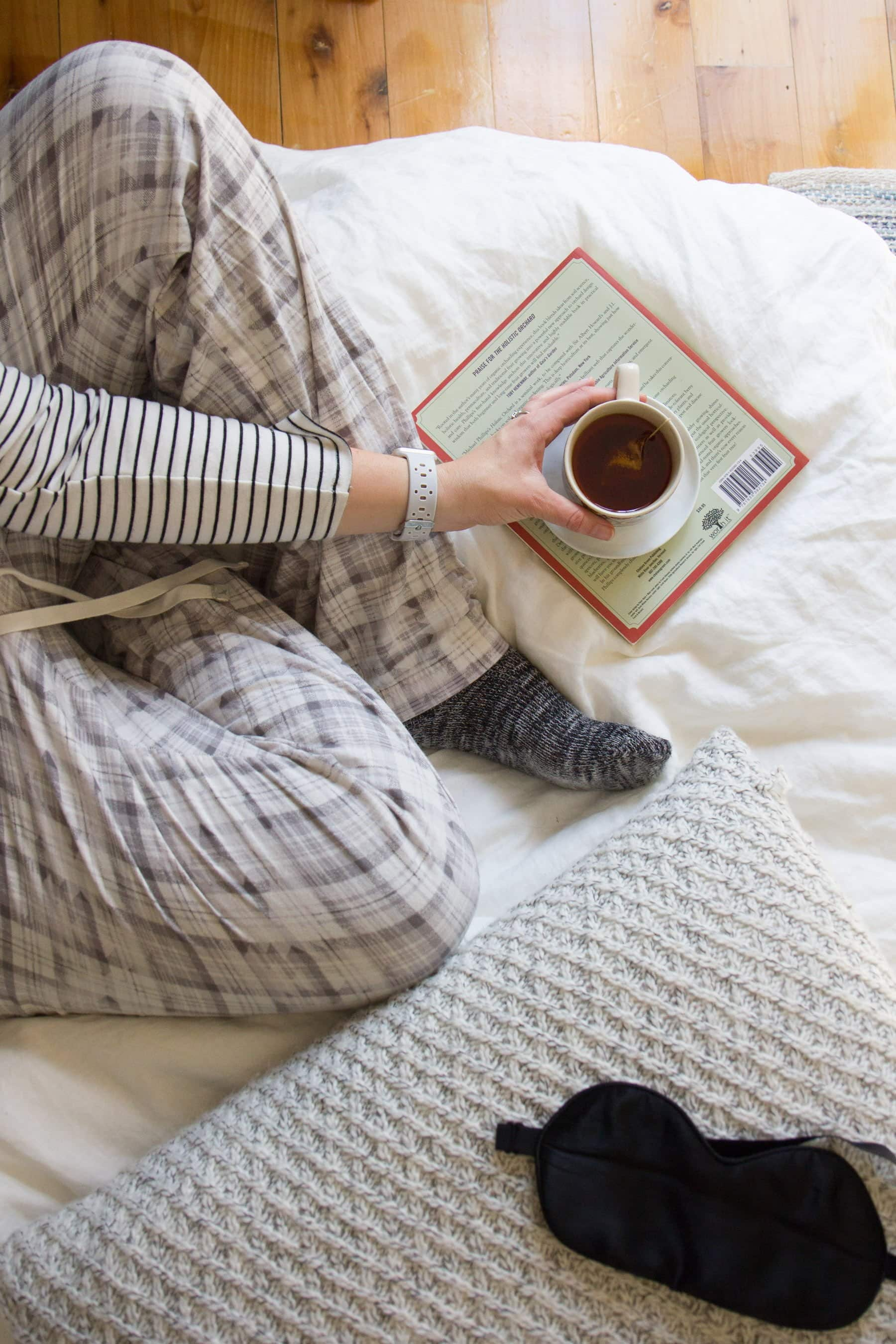 Person in plaid pajama pants sitting cross legged on a bed, holding a mug of tea over a book.
