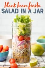 """A glass jar layered with dressing, rice, beans, pico de gallo, onions, tomatoes, cilantro, and lettuce sits on a folded dish towel. Extra ingredients are scattered around the jar. A text overlay reads """"Black Bean Fiesta Salad in a Jar."""""""