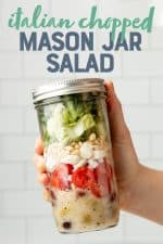 "A hand holds a white-capped mason jar filled with an Italian chopped mason jar salad. A text overlay reads ""Italian Chopped Mason Jar Salad."""