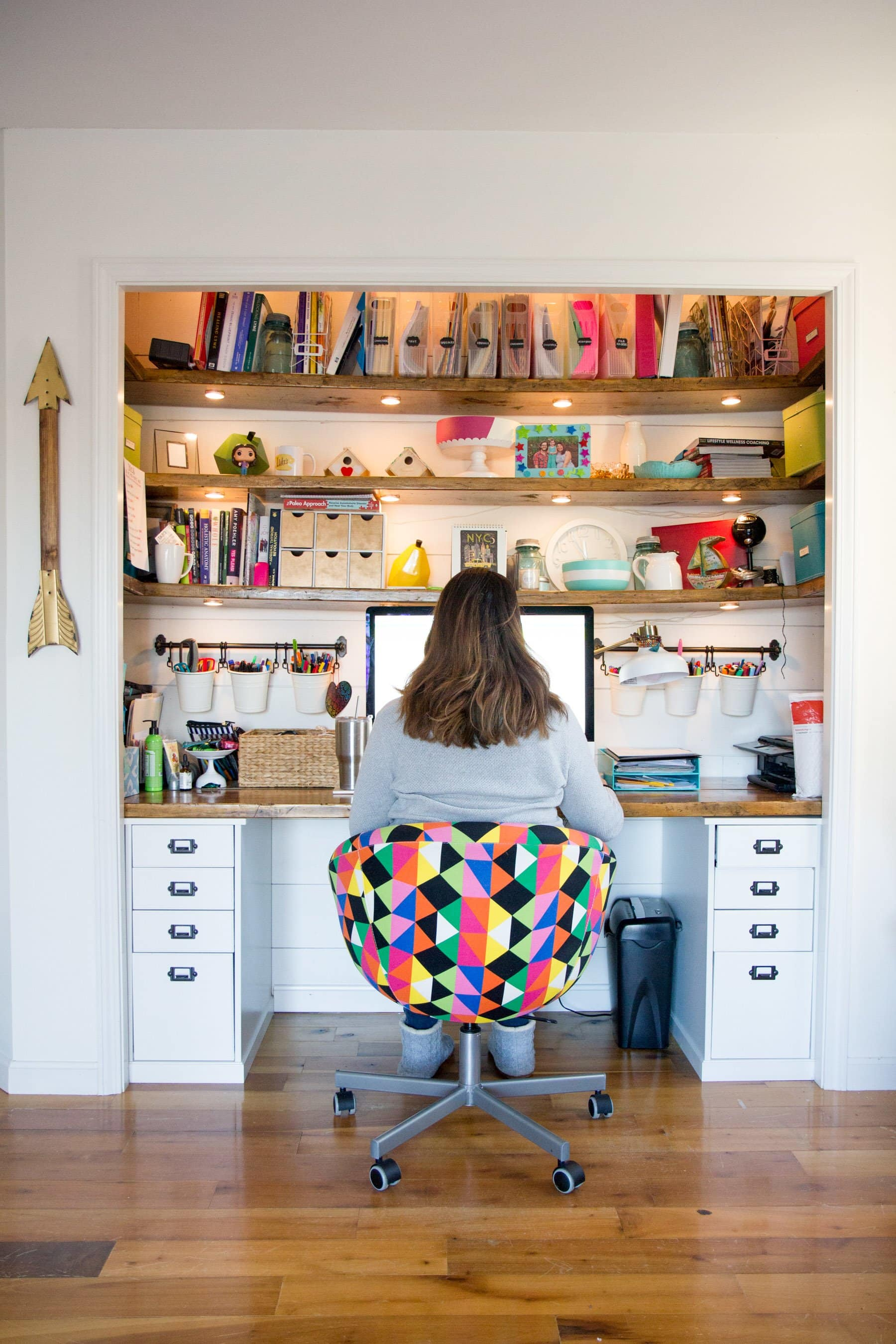 Woman sitting at desk with shelves above full of books