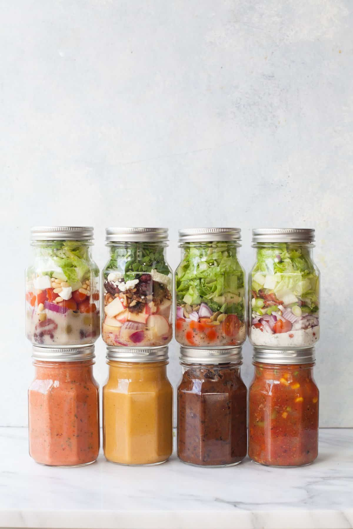 Eight glass mason jars stacked, half with salads, and half with soups on a gray background