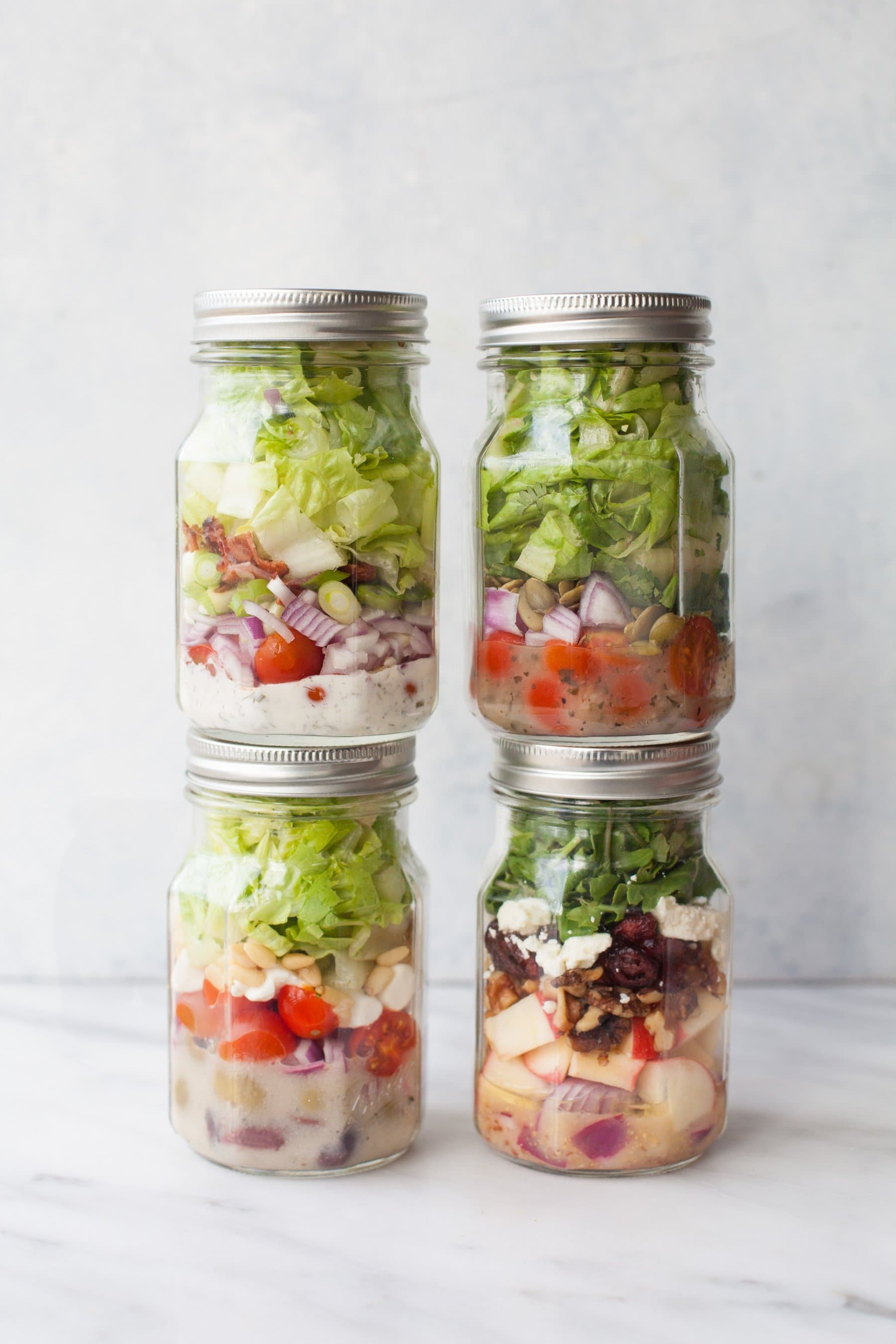 Four glass canning jars filled with salads stacked against gray background