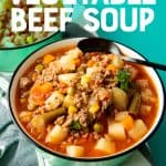 """Two teal bowls of vegetable beef soup sit on a tea towel. A text overlay reads """"Use Your Pantry Staples! Vegetable Beef Soup"""""""