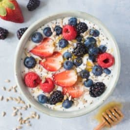 Overhead shot of Instant Pot coconut yogurt in a white bowl, garnished with mixed berries and seeds, and a drizzle of honey
