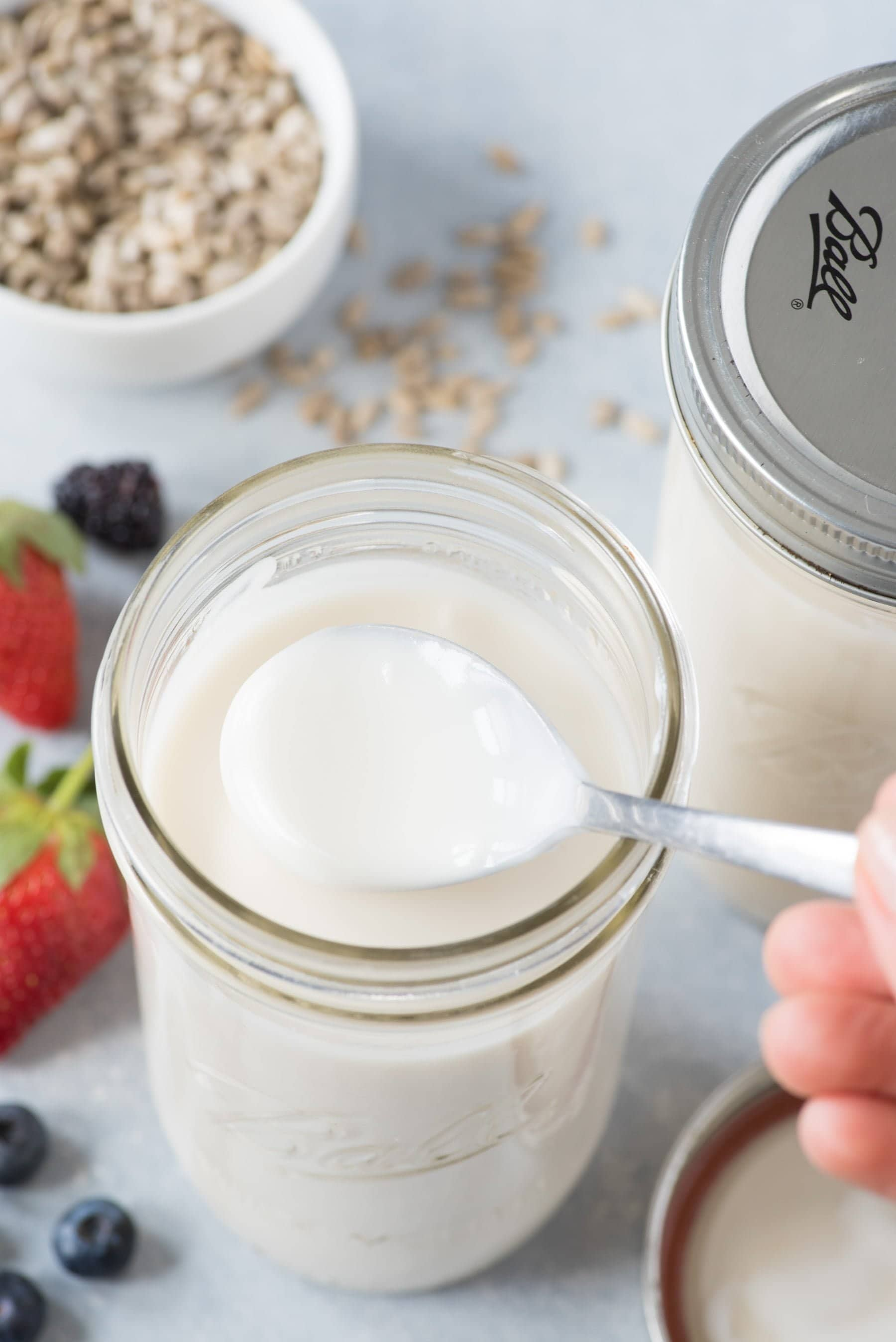 Overhead shot of a spoon scooping Instant Pot Coconut Yogurt out of a Ball mason jar, with another jar, berries, and seeds in the background