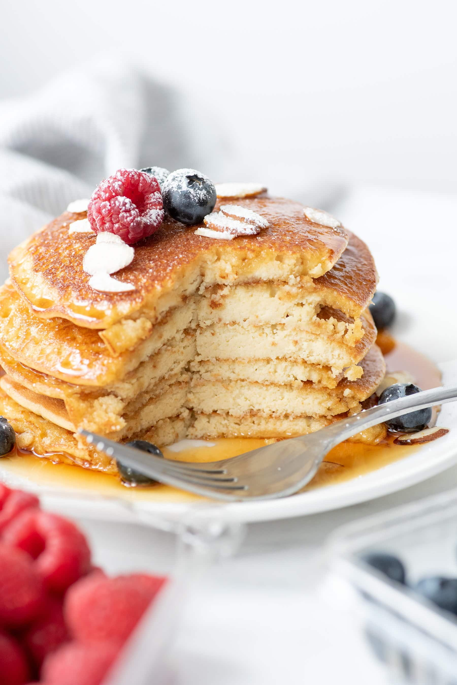 Side shot of a stack of Grain-Free Blender Almond Pancakes, garnished with berries and almonds