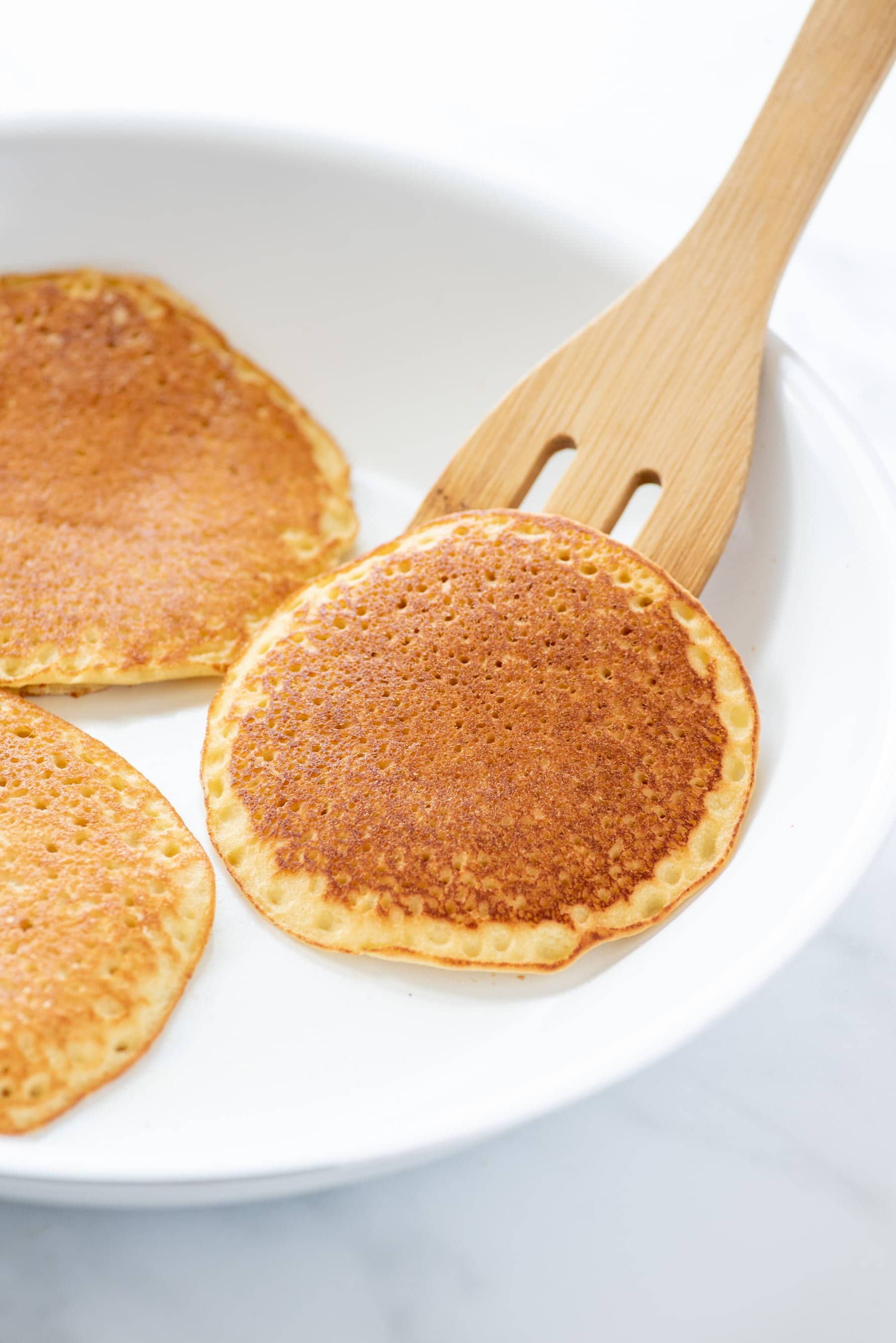 Side angle shot of a wooden spatula sliding a blender almond pancake onto a plate