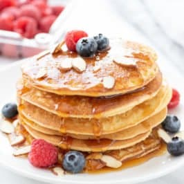 Side angle shot of a stack of grain-free blender almond pancakes, garnished with berries and sliced almonds