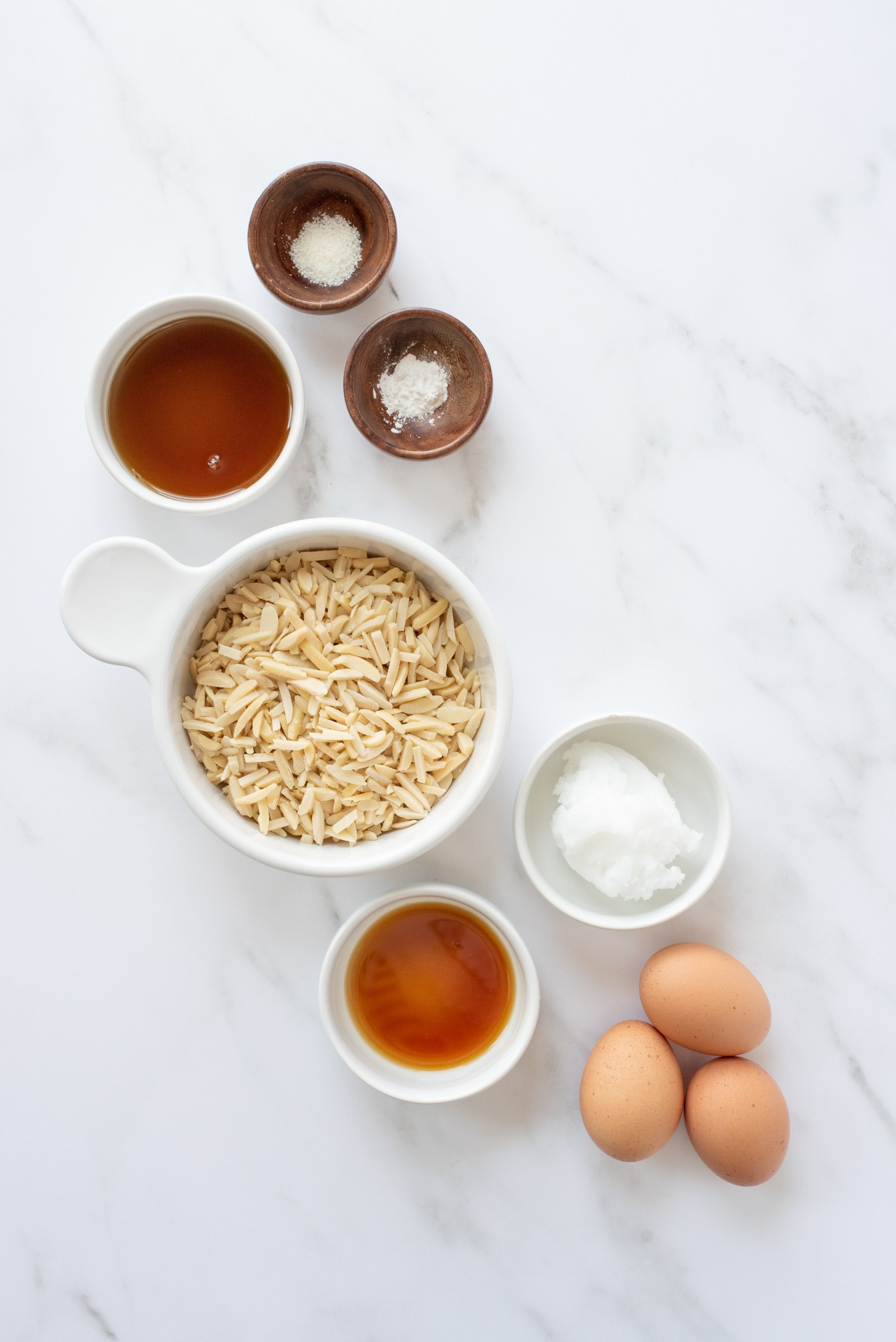 Overhead shot of ingredients for blender almond pancakes - sliced almonds, coconut oil, eggs, coconut oil, and maple syrup