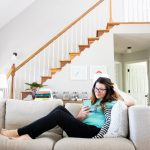 Woman lounging on couch while looking at a phone to find a therapist