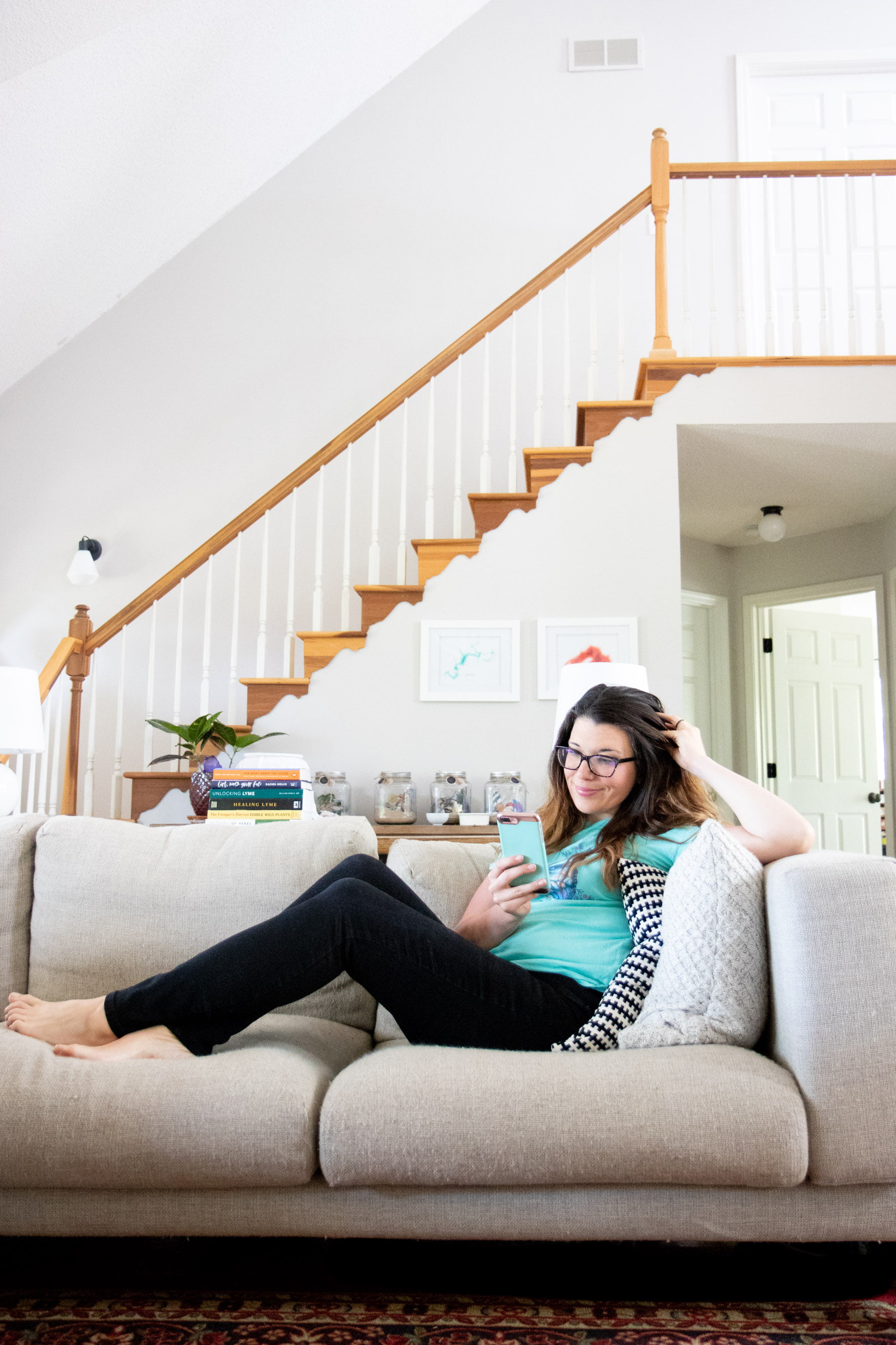 Woman lounging on an off-white couch looking at a phone to find a therapist