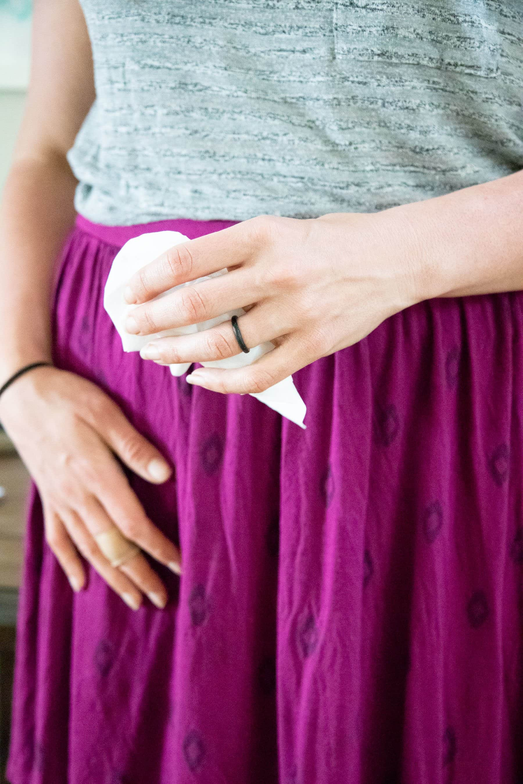 Torso of a woman in a gray shirt and purple skirt holding a tissue, at therapy for the first time