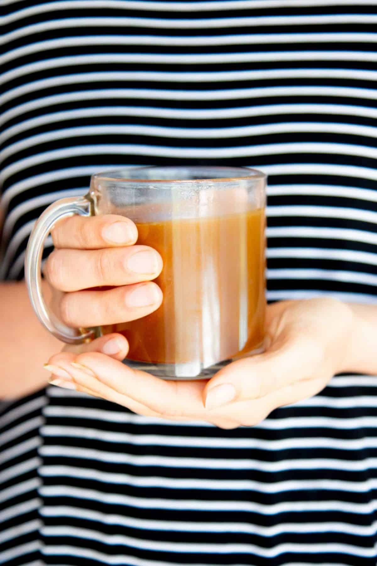 Clear mug of bone broth held in two hands to boost your immune system
