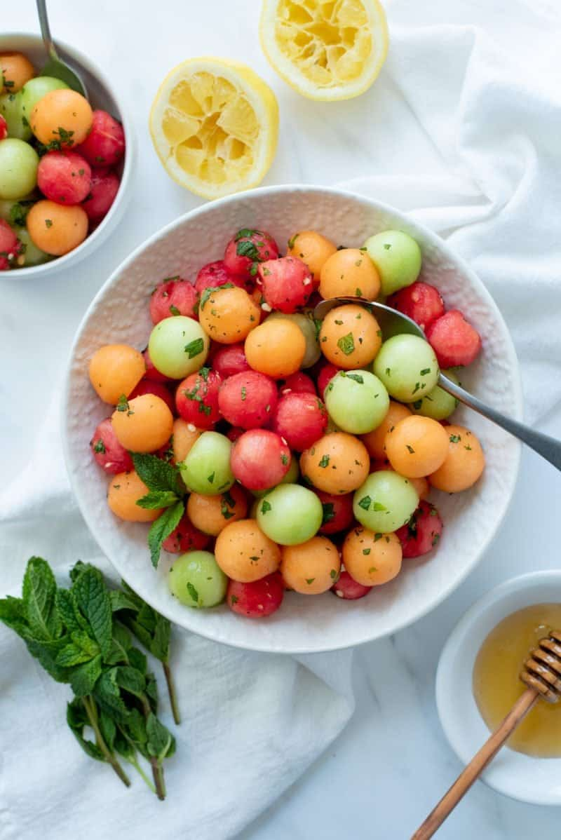 Overhead shot of Honey-Mint Melon Salad in a white bowl with a spoon