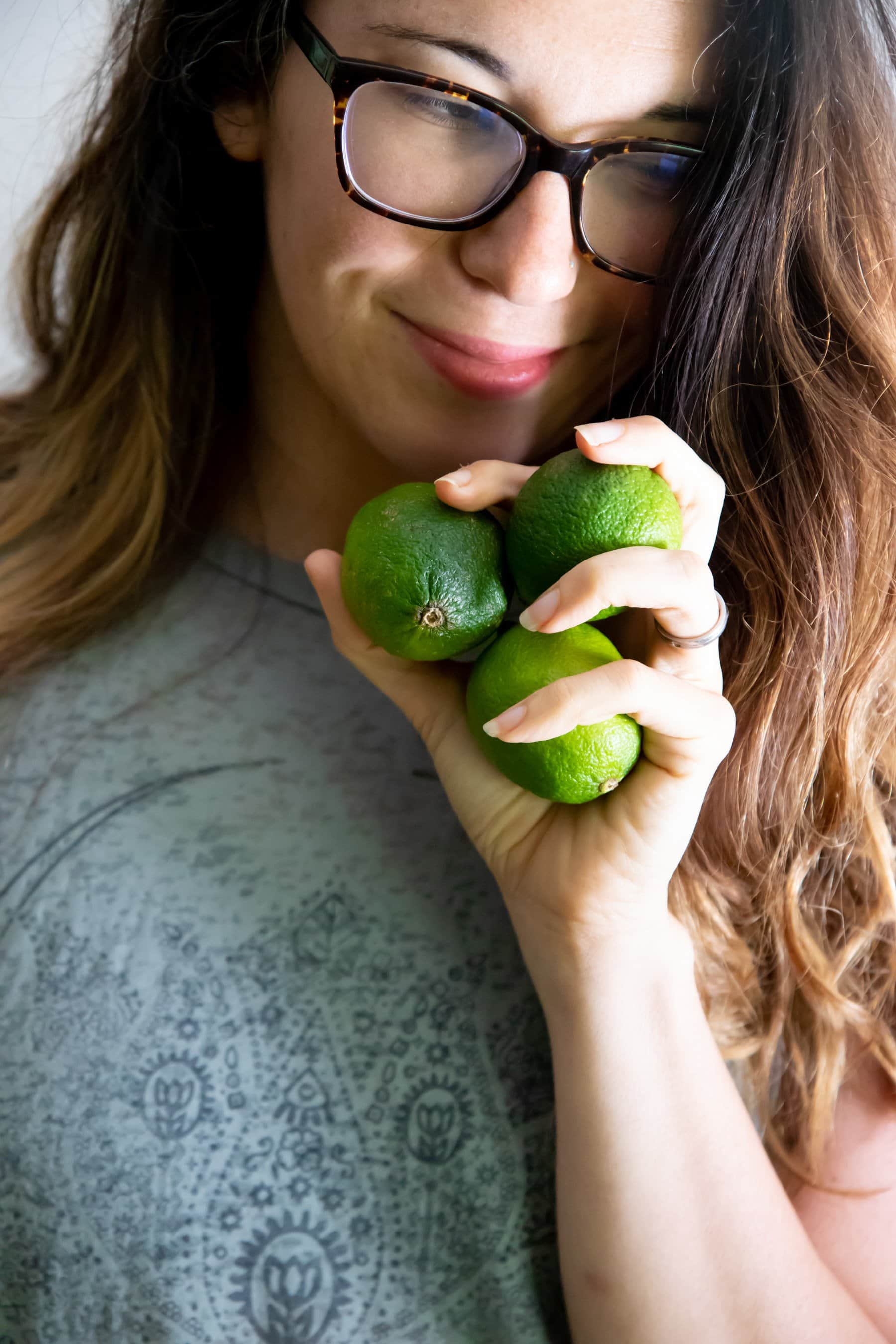 Brunette woman in glasses holding three limes by her face