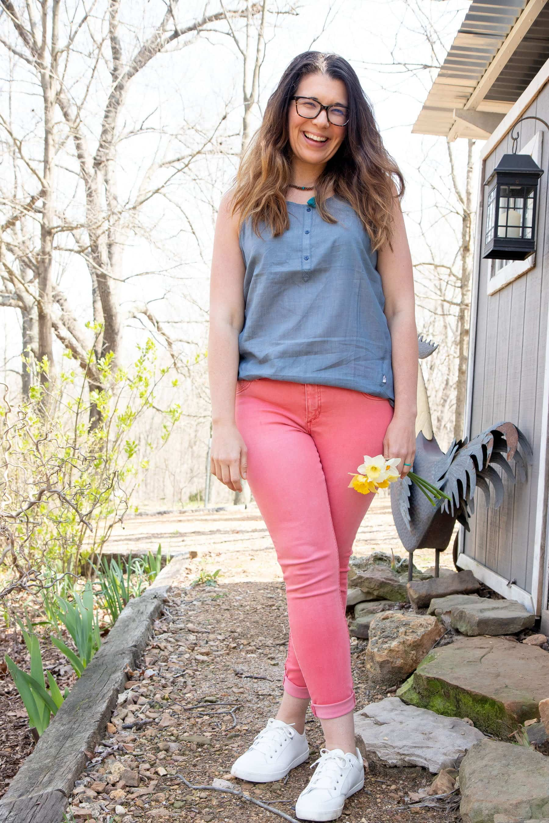 Full body shot of a woman in a blue shirt and pink pants, holding a bunch of daffodils