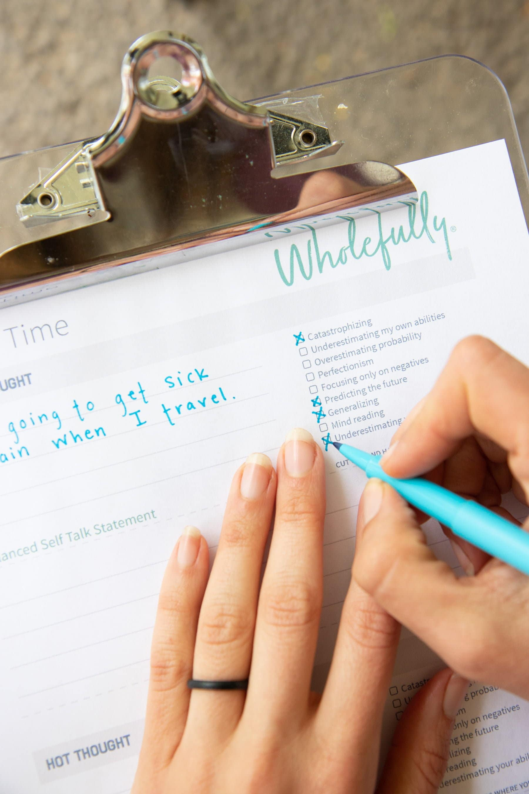 Overhead shot of two hands filling in a Worry Time worksheet with a blue pen and a clipboard