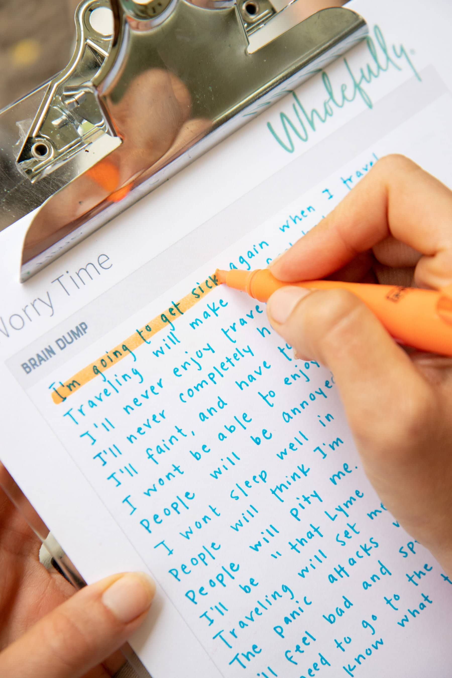 Overhead shot of a hand using an orange highlighter on a clipboard to fill in a Worry Time worksheet, with an iPhone timer running