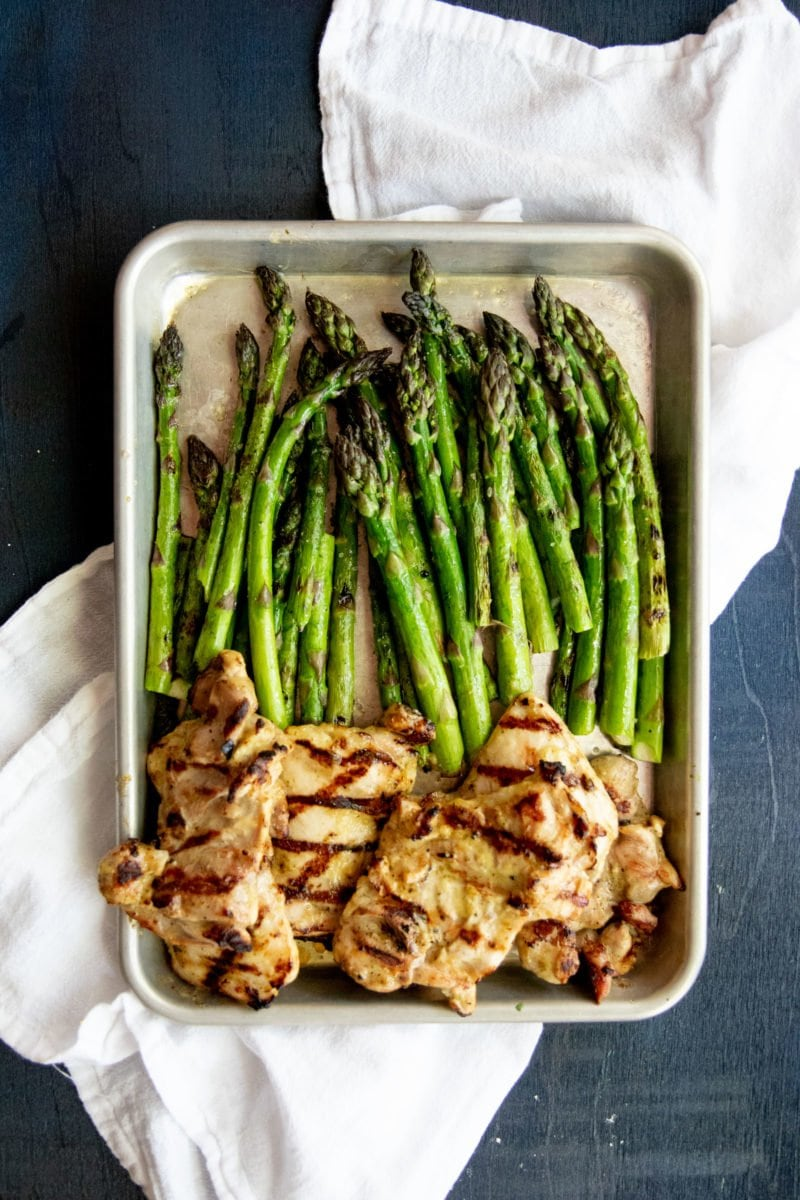 Overhead shot of grilled chicken and asparagus on a baking sheet