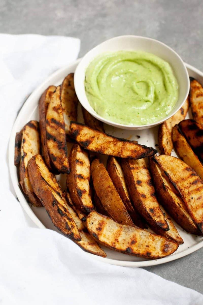 Side angle shot of Perfect Grilled Potato Wedges with a small dish of sauce
