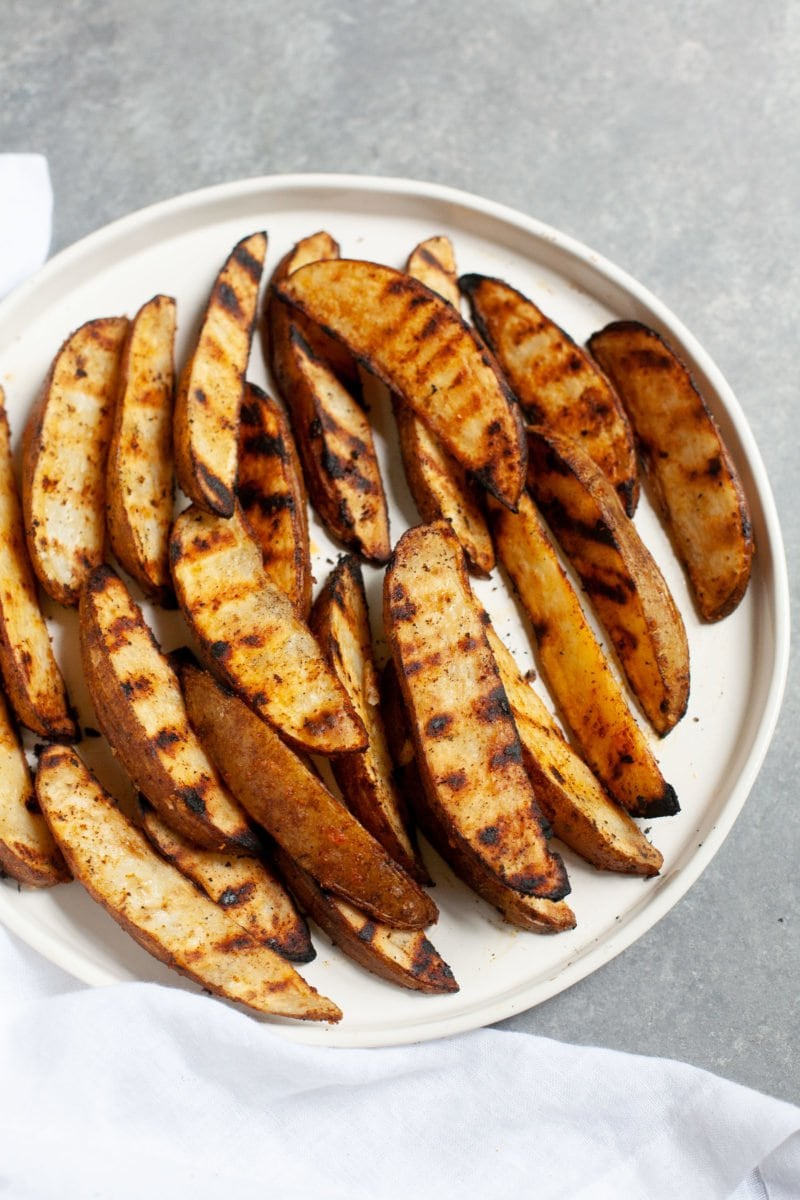 Side angle shot of Perfect Grilled Potato Wedges on a white plate