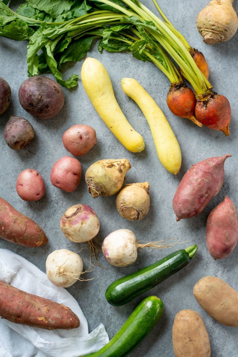 Array of vegetables on a grey background -- sweet potatoes, rutabagas, potatoes, summer squash, zucchini, beets
