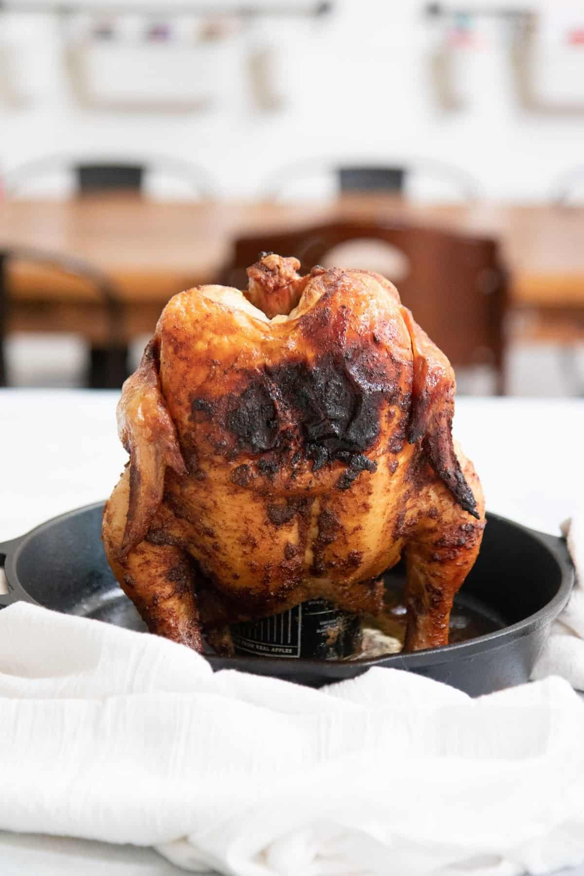 Grilled Beer Can Chicken standing up in a cast iron skillet