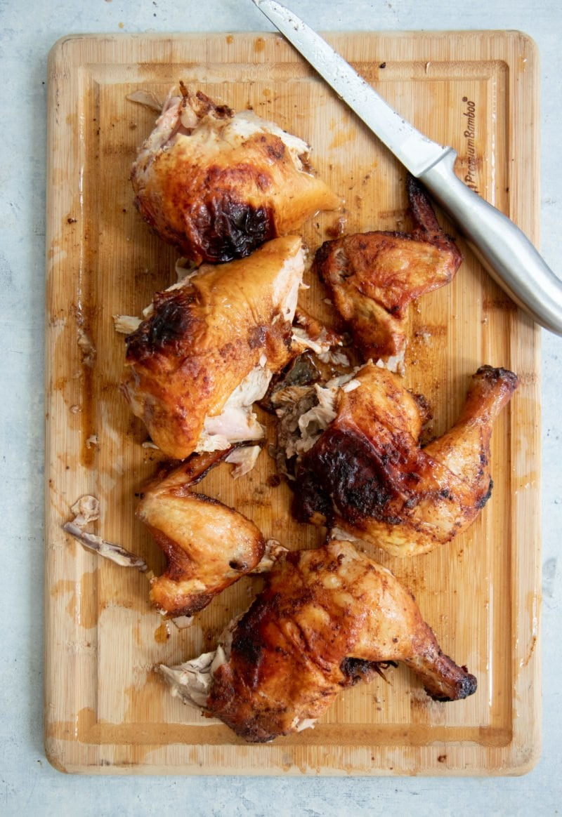 Overhead shot of cut-up grilled chicken on a wooden cutting board